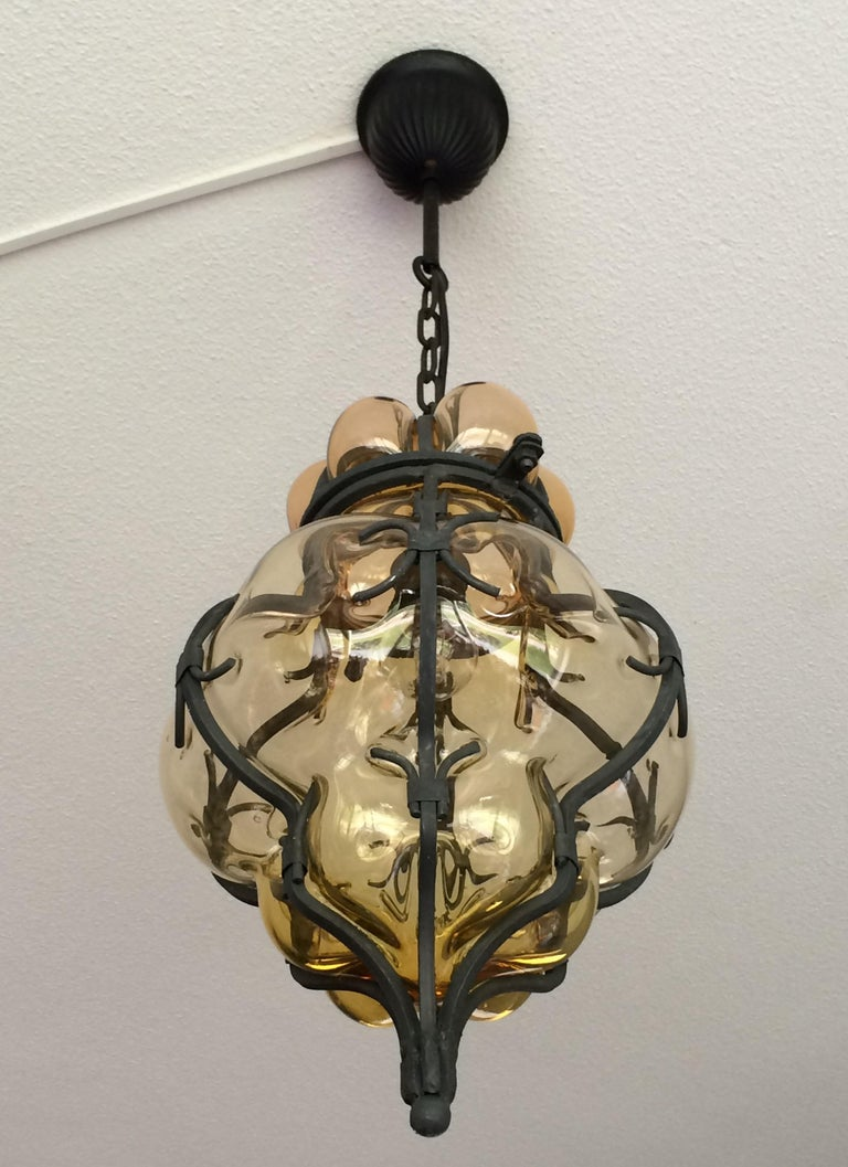 These handcrafted and stylish pendants are in near-mint condition.  This pair of single light, Italian pendants is very beautiful, both in shape and in color. The stunning amber glass is mouth-blown into hand forged, wrought iron frames and the