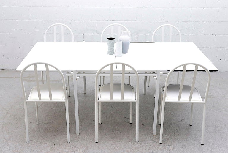 Unique midcentury dining table with double white square table tops and white enameled metal frame. This impressive two tiered dining table doubles in size by aligning both table tops in a sturdy shared groove to make dining space for 6-8 chairs. In
