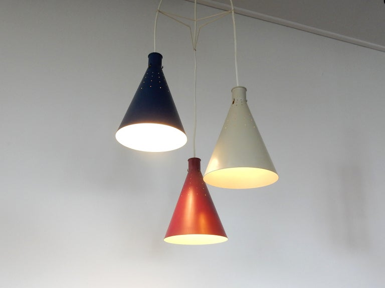 This very good looking set of 3 conical pendant lamps was designed by Alf Svensson for Bergboms in Sweden in the 1950s. It consists of 3 metal shades in red, grey and blue lacquer. The shades are perforated with small holes that gives a stunning