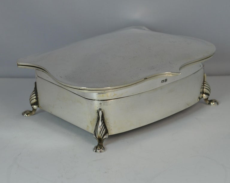 A beautiful English made solid silver jewellery box. Stylish shaped piece with plain finish throughout and standing on four lion feet. Unusual design with top tier for thirteen rings and the tier below plain for chains, pendants etc.  Hallmarks ;