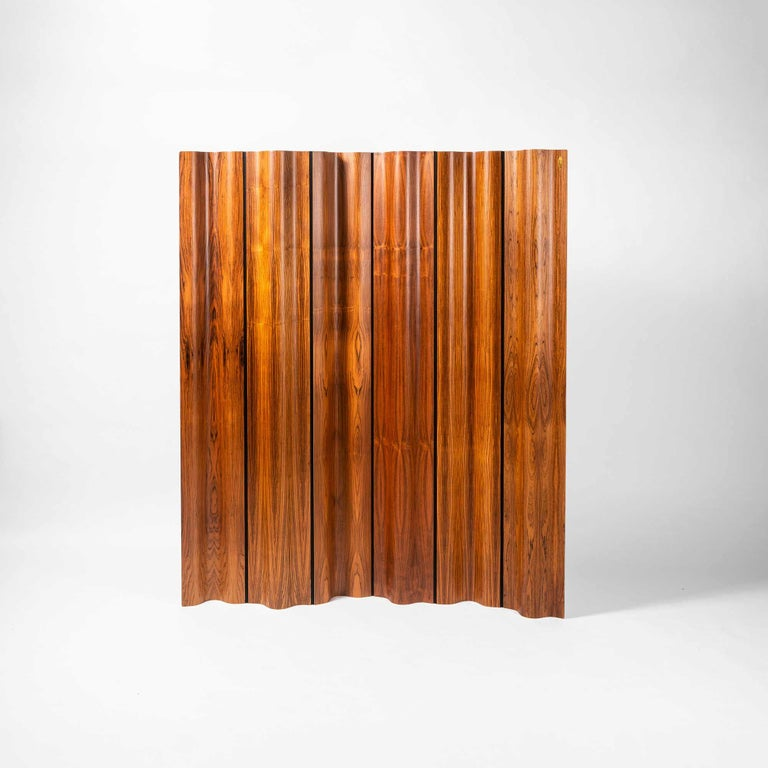 Limited edition of the Eames folding screen (FSW-6) in rosewood, numbered 155/500. The design of the screen was a clever combination of molded plywood panels and a flexible cotton canvas band in between each. The panels were shaped to the same exact