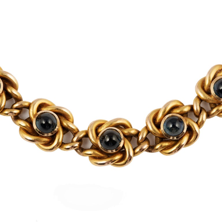 From the Romanov era, period of Nicholas II, the links of solid gold each in a knot design, the front enhanced with five bezel set deep blue cabochon sapphires, with original safety chain. In an original silk and velvet retailer's box stamped