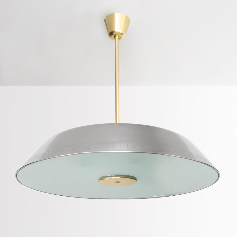 A very rare Scandinavian Modern polished steel and glass pendant designed by Harald Notini made by Böhlmarks, Sweden. This fixture has been completely restored and newly rewired with 6 internal standard base sockets and 3 additional sockets recessed