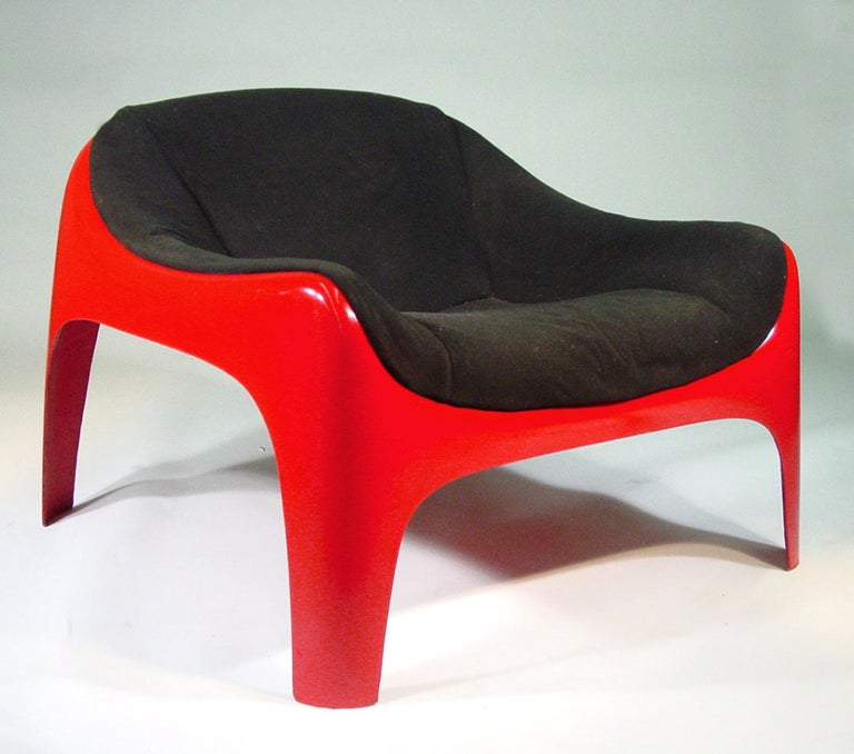 This original mod style lounge chair was designed by architect and Artemide co-founder, Sergio Mazza in the 1960s. The chair features a stunning red fiberglass frame with a removable upholstered black seat cushion.