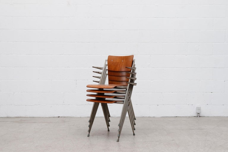 Amazing and rare set of 4 Wim Rietveld stacking 'Pyramid' armchairs. Extremely durable and comfortable with grey enameled metal frames and arms rests. Formed teak seat and backrest Riveted to the folded sheet metal frames. These 1960 'Signe D'or'