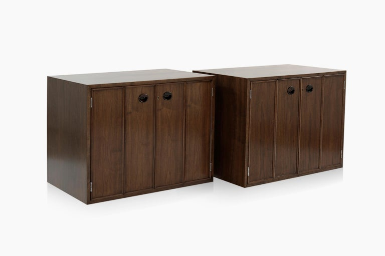 Set of fully restored floating cabinets in walnut designed by Edward Wormley for Dunbar, circa 1950s. Bi-fold doors open up to reveal two shelves, proving ample storage space for books or silverware / flatware. Rosewood pulls add a touch of elegance