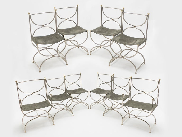Beautiful set of 1960s Curule Savonarola chairs made of heavy stainless steel metal with brass accents. This incredible set of eight chairs plus two chairs with armrests was created by French interior design firm Maison Jansen. The sparse original
