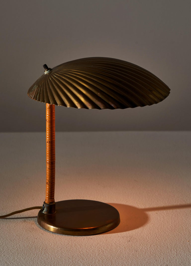 Rare Simpukka table lamp by Paavo Tynell for Taito Oy. Manufactured in Finland in 1941. Simpukka translates to clam. Solid brass shade and base with rattan wrapped stem. Original cord. Retains original makers stamp. Takes one E27 candelabra 60w