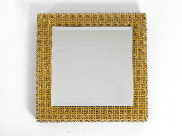 Beautiful background illuminated brass metal mirror from the early 1960s by Palwa. Made in Germany. Very rare in this square design with a high frame full of crystal stones. Great glare-free light. Very thick, massive cut mirror glass. Mirror