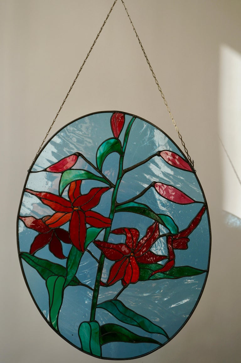 Beautiful 20th century oval stained-glass window panel with red flowers in vibrant colors.