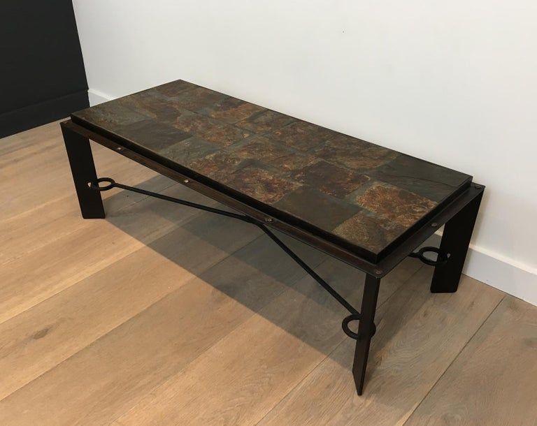 This unique and beautiful coffee table is made of steel and iron with a lava stone top. This is a very interesting design with forged iron and large rivets all around the top frame. The top is made of beautiful patchwork lava stone tiles. This is a