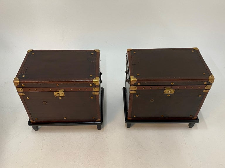 Superb pair of early 20th century leather bound military trunks with handsome brass mounts, studs and hardware and dark blue fabric lined interiors. Each rests on a custom stand so perfect for end tables or night stands.