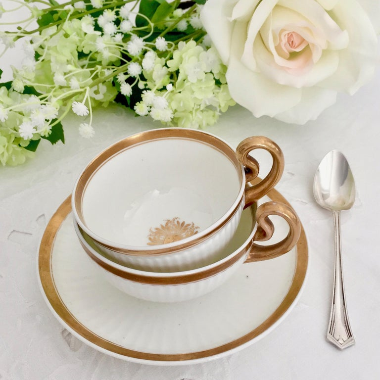 On offer is a beautiful porcelain tea set made by Swansea around the year 1820, which was the Regency era. The set consists of a white and gilt decorated teacup and a larger