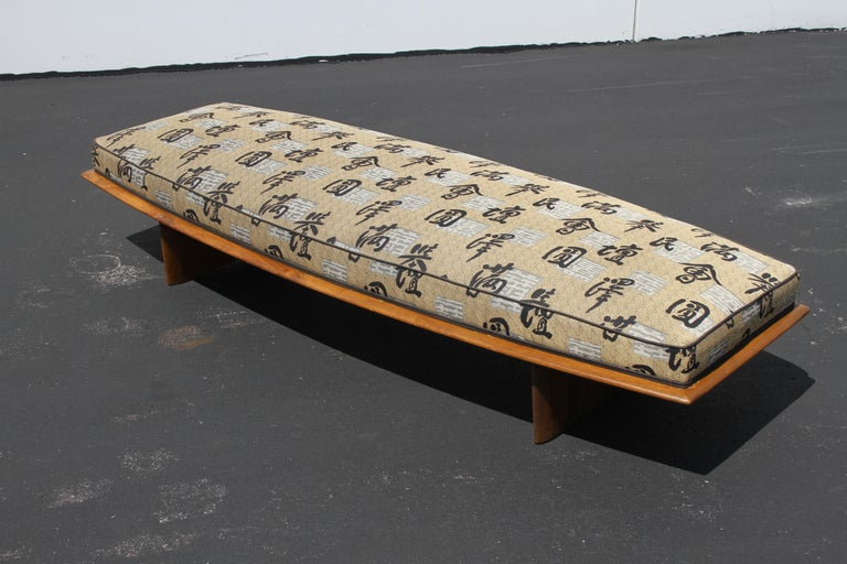 Rare T. H. Robsjohn-Gibbings for Widdicomb daybed, boat shaped upholstered form on plinth tapered legs and tapered wood surround. Shown in original finish with older reupholstery. Price includes wood frame refinishing prior to shipping, custom stain