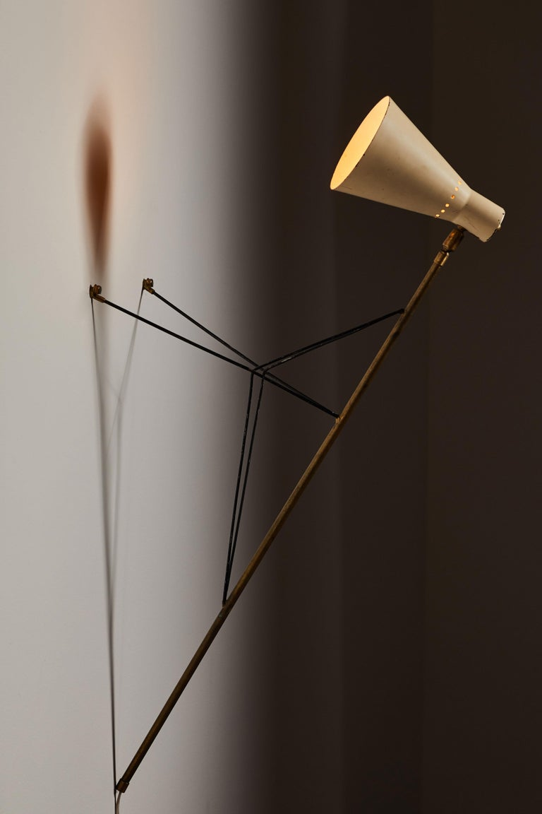 Rare table or wall light by Stilnovo. Manufactured in Italy, circa 1950s. Brass base, enameled metal shade. Can be mounted on wall or used as a table lamp. Original cord. Takes one E27 60 W maximum bulb. Retains original manufacturer's label.