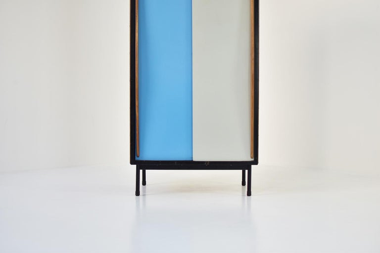 Rare two-tone cabinet by Willy Van Der Meeren for Tubax, Belgium, 1952. This Modernist cabinet has 2 lacquered metal sliding doors with elegant wooden handles. On the left a coatrack, on the right three open shelves. This storage cabinet is in