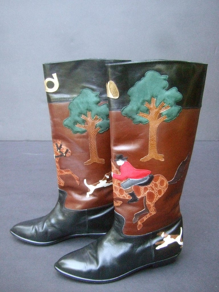 Rare unique hunt scene leather & suede applique boots designed by Beverly Feldman c 1990 The stylish black & brown leather boots depict a pair of hunters wearing red suede jackets; mounted on brown embossed applique leather horses; surrounded by