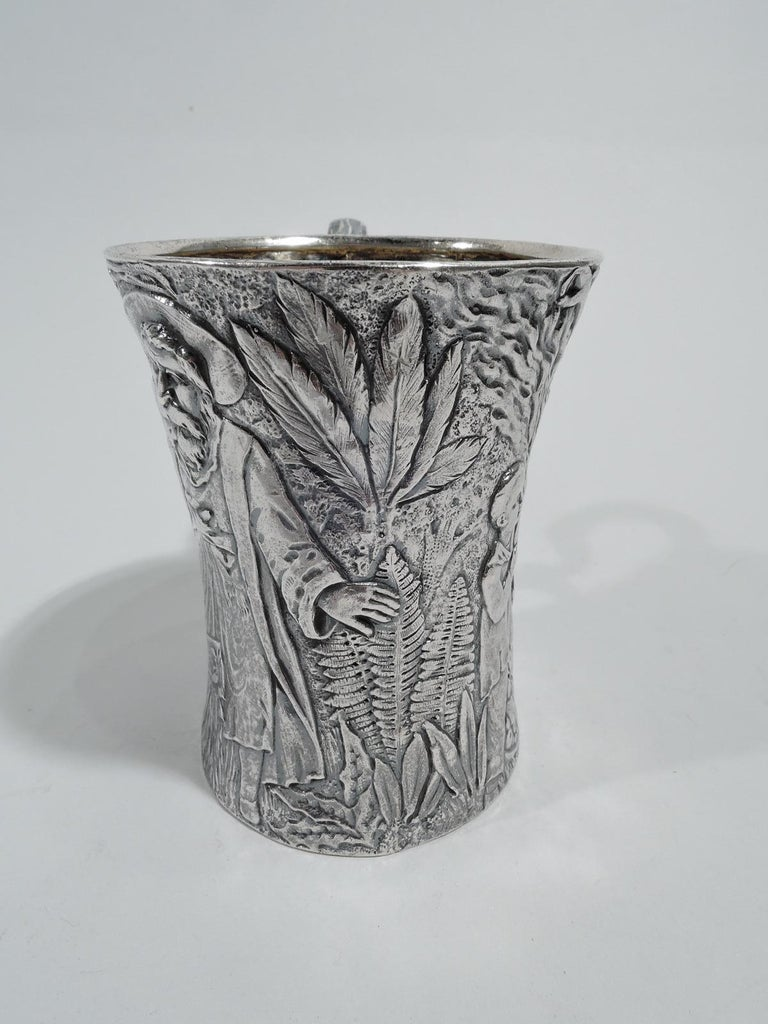 Unusual sterling silver baby cup. Made by Tiffany & Co. in New York. Tall and waisted with dense low-relief frieze depicting 2 boys, one holding a genie lamp and the other heaving a case out of the ground, as well as 2 magical or divine figures of