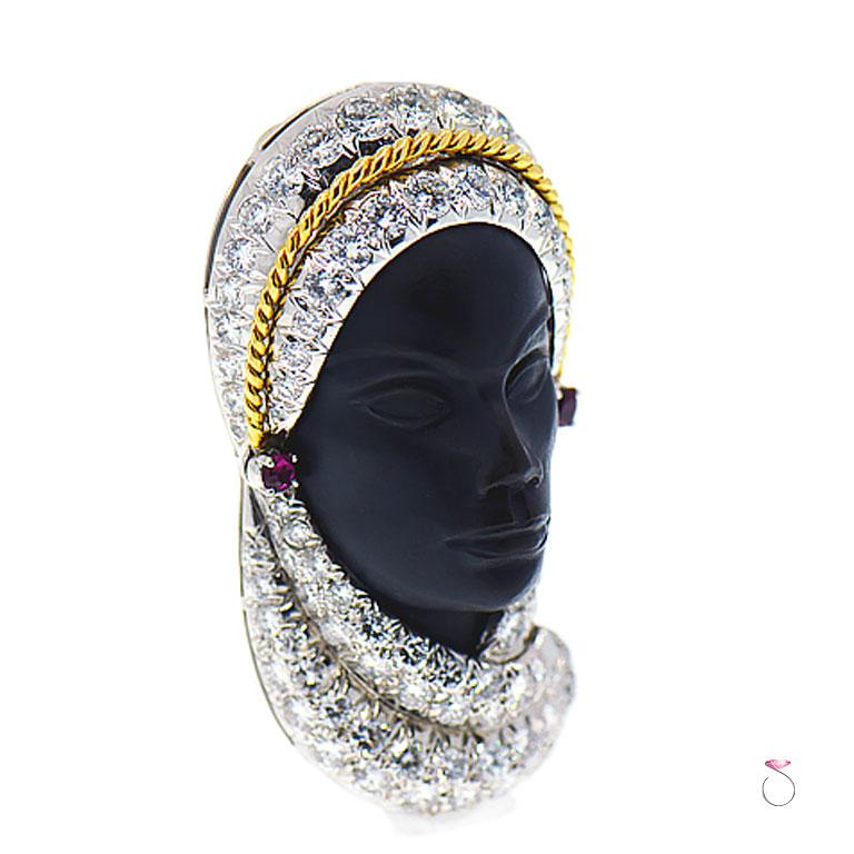 This veiled lady brooch is superbly crafted in platinum and 18K yellow gold, with approximately 4.60 ct micro pave round diamonds on her veil. She has ruby earrings totaling approximately 0.10 ct. Her face is carved in Ebony with stunning details