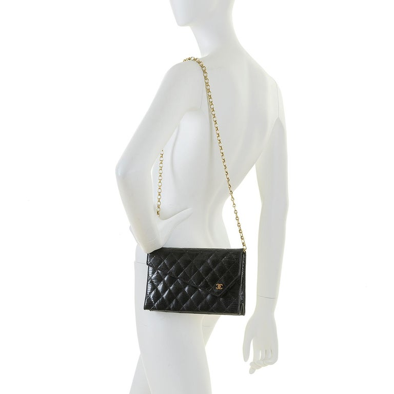 This rare Chanel black quilted, lizard clutch evening bag, designed by the legendary Karl Lagerfeld, is in excellent condition throughout. The classic envelope design is accented with gold hardware, highlighted with a gold iconic double 'C'  clasp