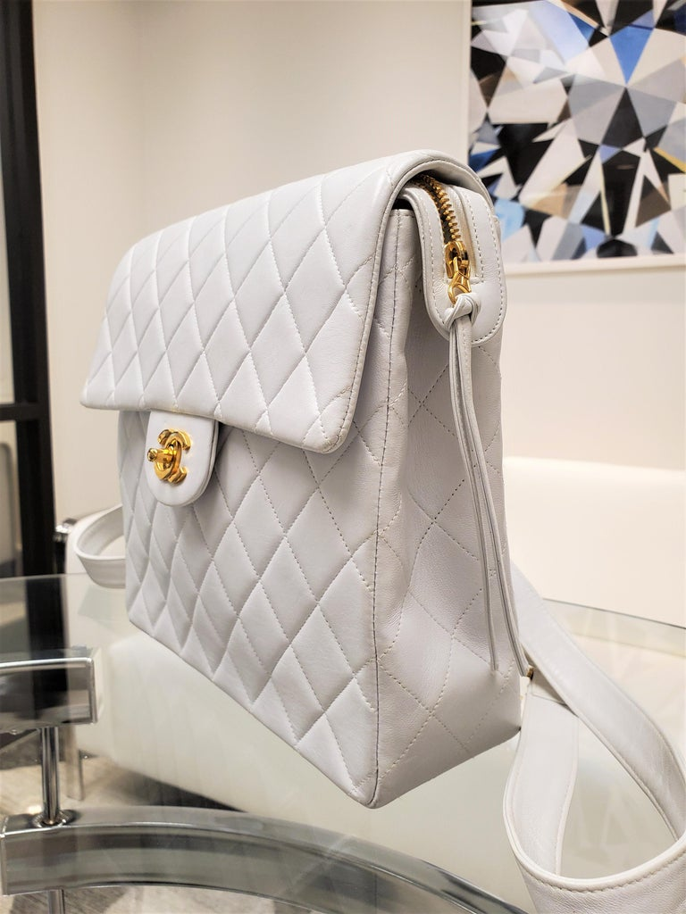 Brand - Chanel Collection - Classic Flap Primary Material - White quilted lambskin leather Hardware - Polished goldtone Pockets - Single exterior pocket at back & dual pocket interior Interior - White lambskin leather Strap - Dual flat shoulder