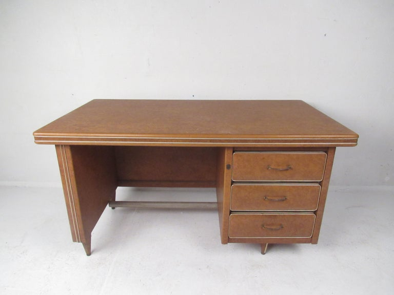 This beautiful Mid-Century Modern desk is covered in a smooth synthetic material with metal trim wrapped around the top. An unusual design with three hefty drawers ensuring plenty of room for storage. The sculpted brass drawer pulls, stubby legs,