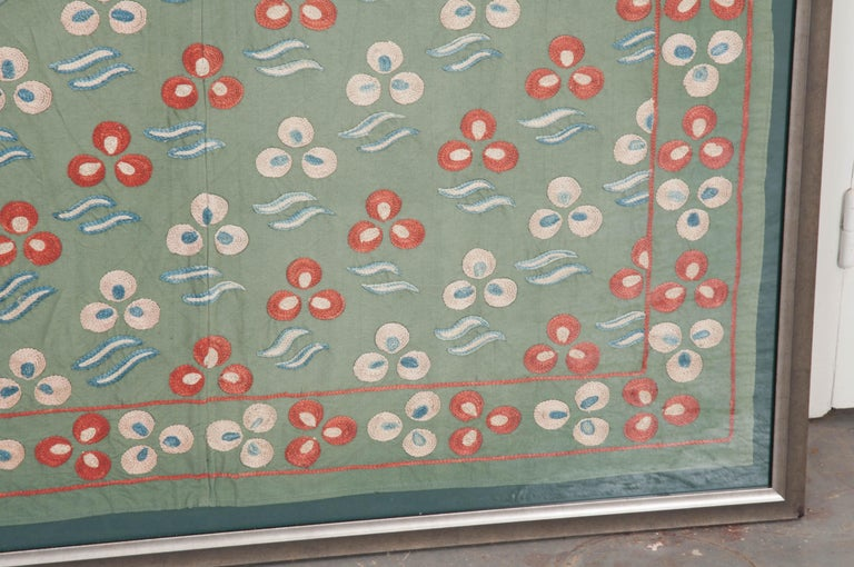 """A rare, vintage """"Nim Suzani"""" hand-embroidered textile panel, in a """"flower-and-wave"""" pattern, from Uzbekistan, circa 1920s, mounted on a forest-green mat, behind glass, and presented in a silvered wooden frame. The ground is a lightweight"""