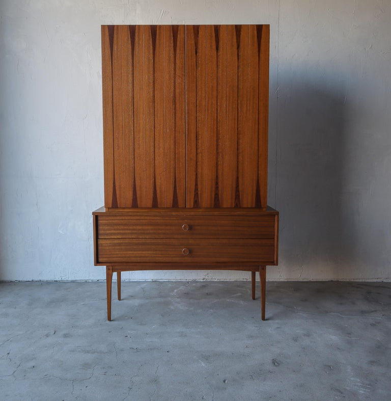 Super rare and early midcentury, armoire by Lane. This piece is absolutely beautiful.It's a stunning combination of walnut and rosewood with brass pulls that too are inlaid with rosewood. A gorgeous and feminine piece supported by 4 tall tapered