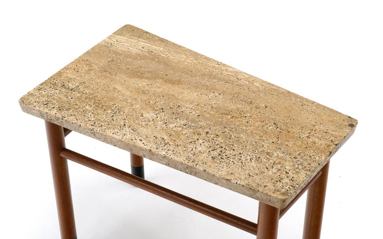 Unique asymmetrical wedge shape side / end table with original Italian travertine top, mahogany legs with black leather wrapped feet. Super rare, early table. Signed with the green Dunbar metal tag.
