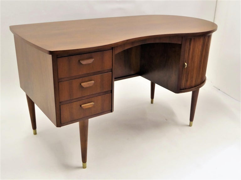 From Denmark, this rarely seen biomorphic double sided teak desk was designed by Gunnar Nielsen Tibergaard. It dates from 1954 and features three drawers on the left with wood pulls. The curved side has two tambour doors that slide and open to
