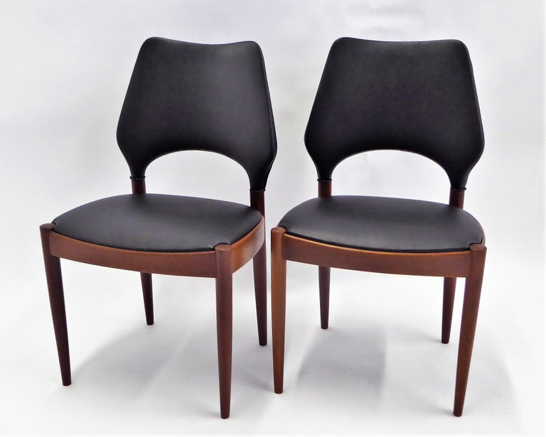 A fine pair and very rarely seen teak side or dining chairs by Arne Hovmand Olsen in 1958 for Mogens Kold Mobilfabrik in Denmark. Beautiful older teak. Re-upholstered in leatherette. The chairs have an exceptionally designed form with exciting