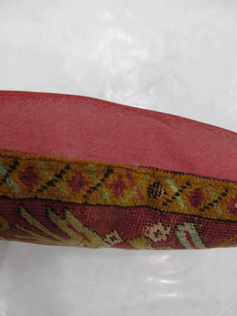 Pillow made from a 19th century Turkish Ghiordes rug backed in red cotton. Measures: 16'' x 18''.