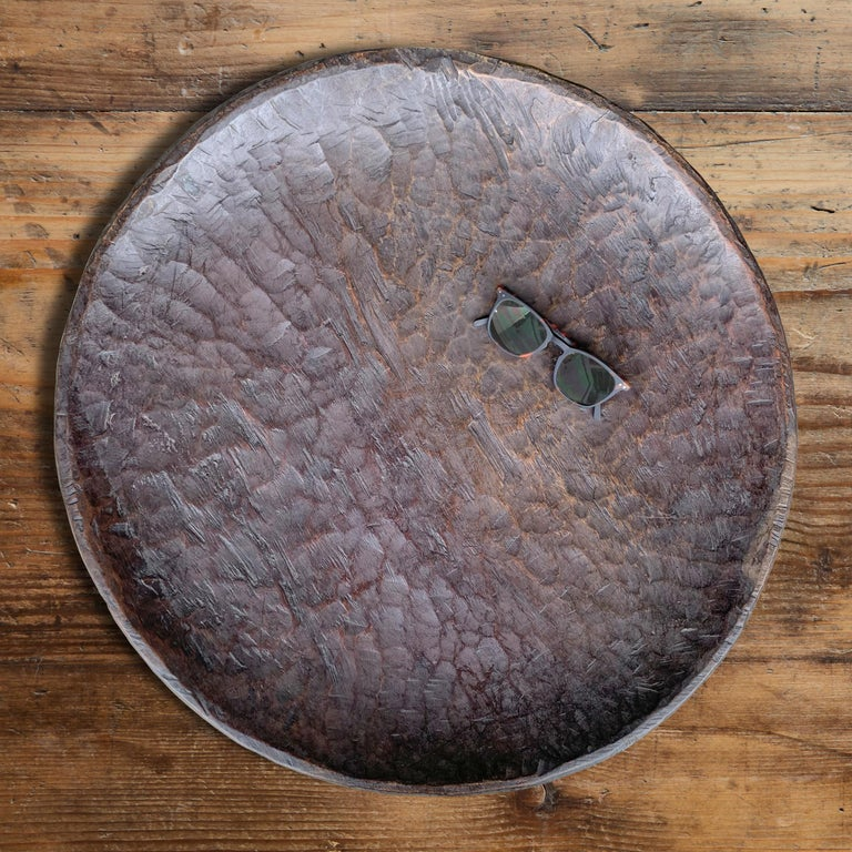 A rather large early 20th century East African hand carved wooden platter with wonderful deep cut marks and fantastic patina. A string loop on the back allows it to be hung on a wall.
