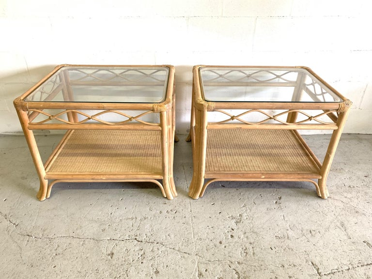 Pair of rattan end tables feature glass top woven wicker lower shelf. Perfect touch of island style to any decor. Good condition with minor imperfections consistent with age.