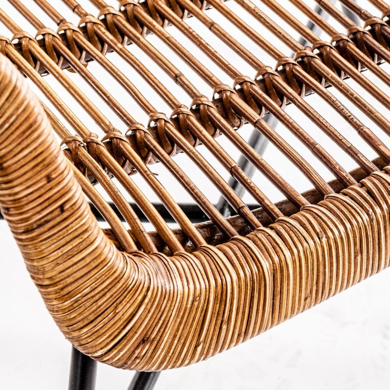 A must-have for any lover of vintage style and natural fiber: armchair composed of a airy structure in rattan shell and black metal feet.