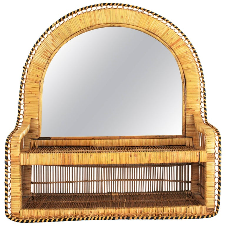 Eye-catching Spanish handwoven bicolor rattan and wicker shelf mirror in the style of the Emmanuelle peacock chair. Spain, 1970s. The frame has a semi oval shape and a meticulous handcrafted work that makes this piece highly decorative and full of
