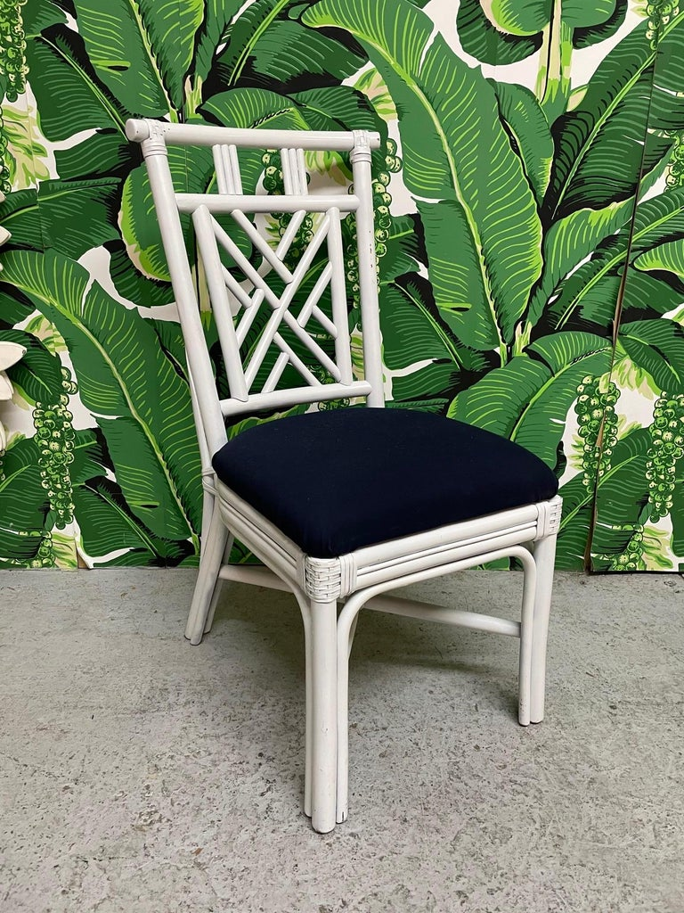 Set of ten vintage rattan dining chairs in Asian chinoiserie style. Six chairs have white upholstery and four have dark blue. Good condition with minor imperfections consistent with age.