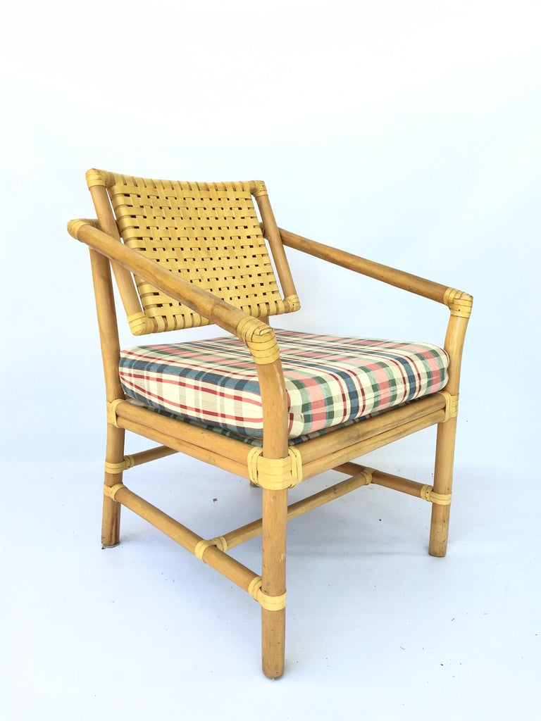 This set of rattan dining chairs features woven leather strap backs and plaid seats. Seat backs tilt for comfort. Very good condition with only minor age appropriate wear. Seat width is 19