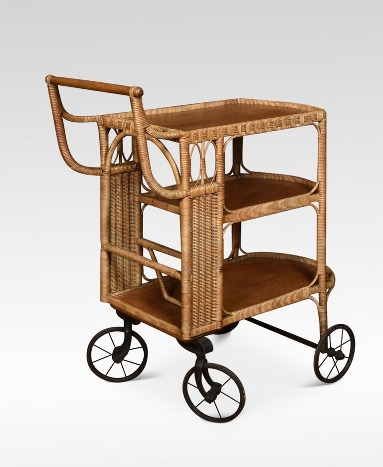 Rattan cane and oak drinks cart or drinks trolley. Featuring a three-tiered body with decorative accents – the top tier with a gallery and handle over two further tiers with inset oak shelves all raised up on four spoked wheels. Dimensions: Height