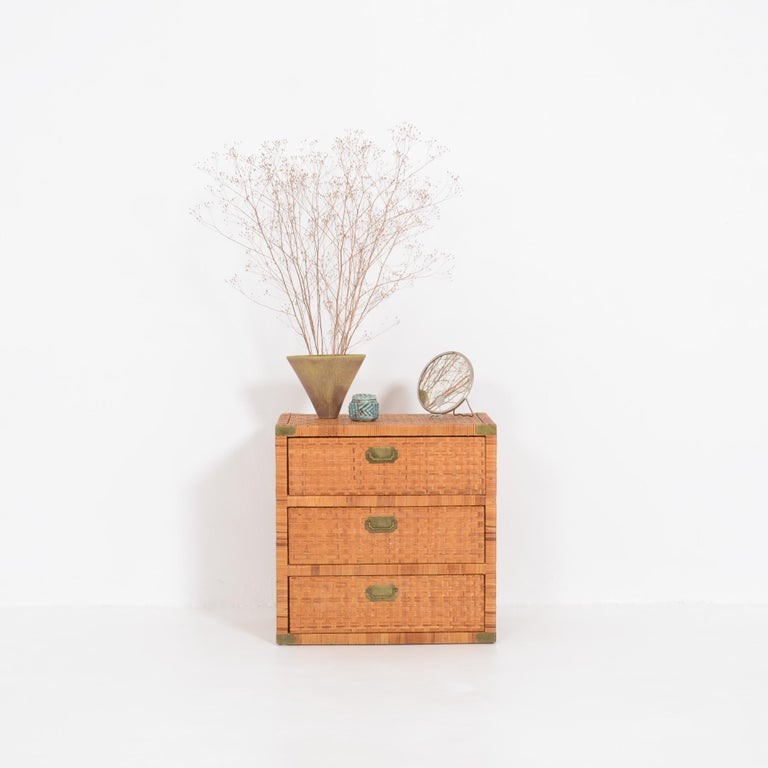 This rattan chest of drawers can be dated in the 1960s. The 3 rattan drawers are finished with copper handles, placed asymmetrically. It is a functional and decorative piece. This vintage chest of drawers is in very good original condition, with