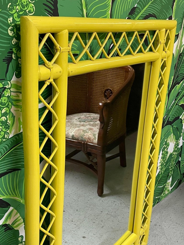 Vintage rattan wall mirror features intricate fretwork and a bright, cheery yellow lacquered finish. Good condition with only very minor imperfections consistent with age.