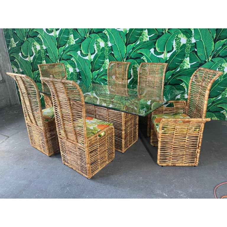 Unique dining set consists of 6 rattan rope wrapped dining chairs upholstered in a tropical palm leaf print and matching pedestal table with glass top. Steel frame construction, heavy and sturdy. Two armchairs and four side chairs. Very good vintage