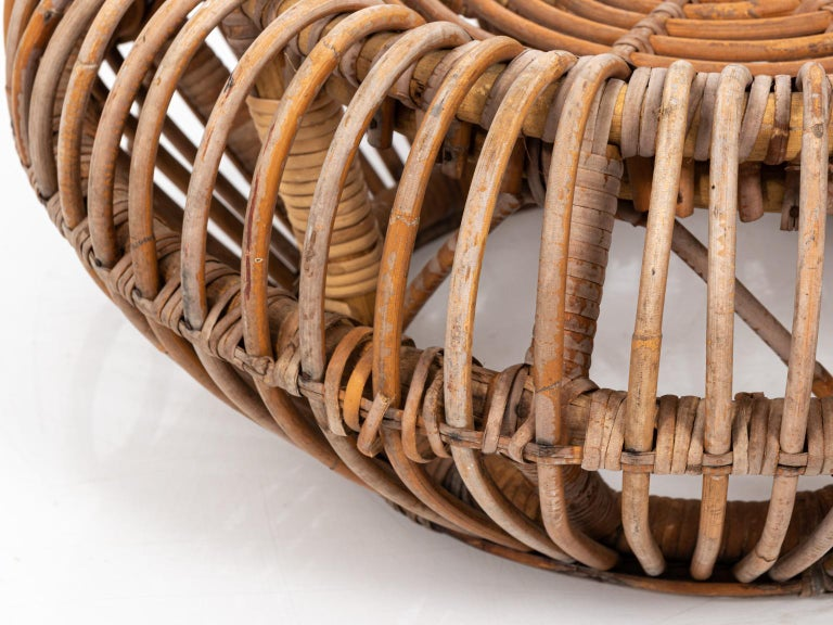 Woven rattan ottoman in the manner of Franco Albini, circa 1960s. Please note of wear consistent with age including repairs to the rattan and minor fading.