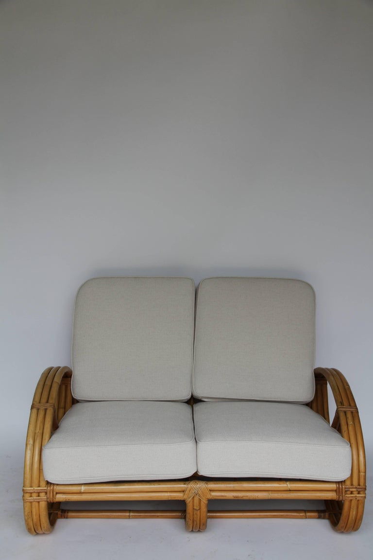 Three-strand round pretzel arm rattan loveseat in the style of Paul Frankl, with custom-made cushions.