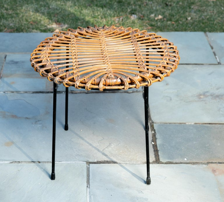 Rattan round side table with black metal base.