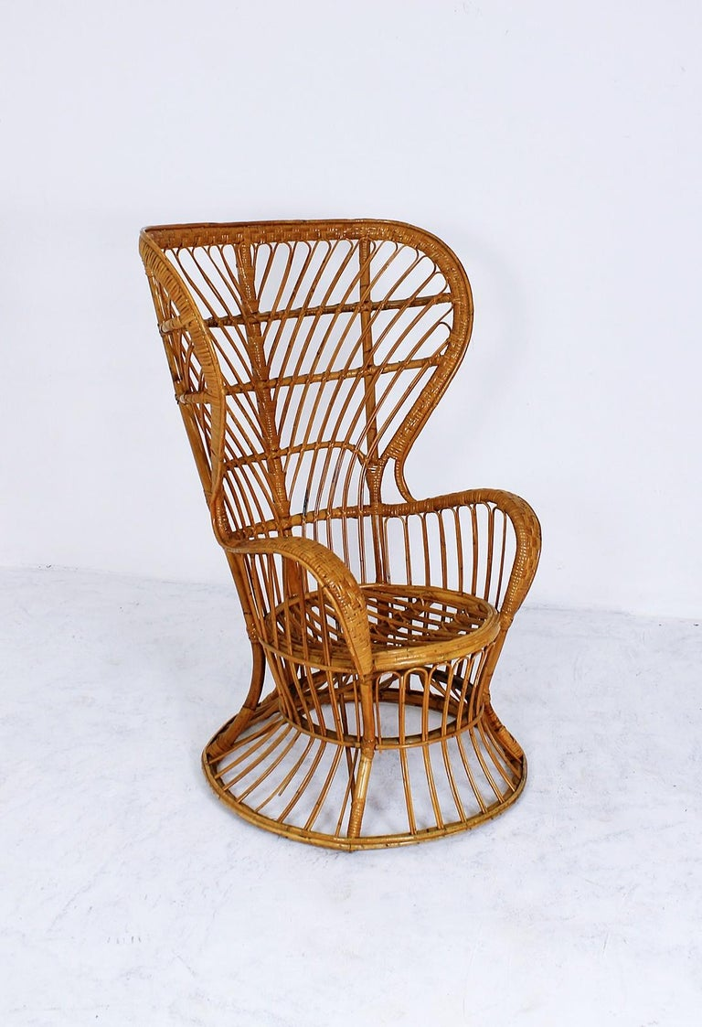 This Italian handcrafted midcentury rattan high back armchair was designed by Lio Carminati in the 1950s and manufactured by Pierantonio Bonacina. The item was specifically designed for the cruise ship Conte Biancamano.  Wear consistent with age and