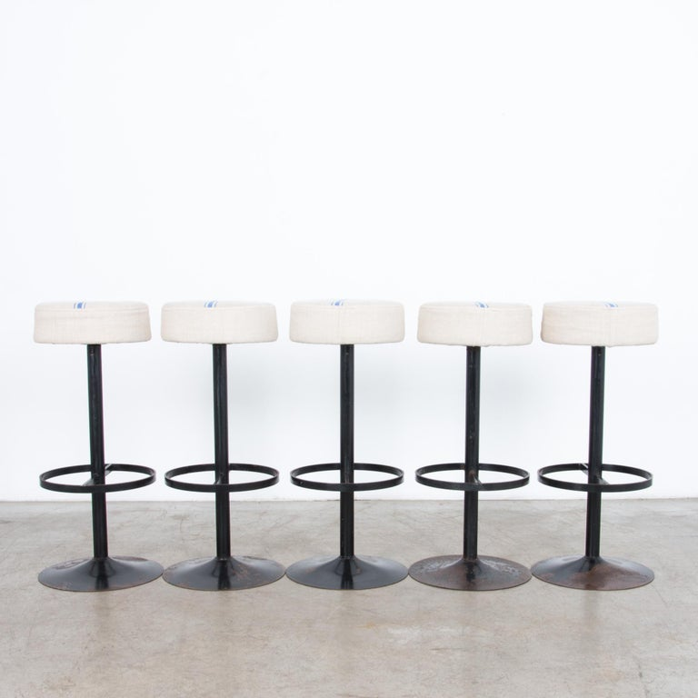 From 1970s Belgium, six sleek steel stools with a minimal designed base topped with a blue striped fabric seat. Oxidised black enamel, updated and polished with unique upholstered tops cut from vintage patterned linen.