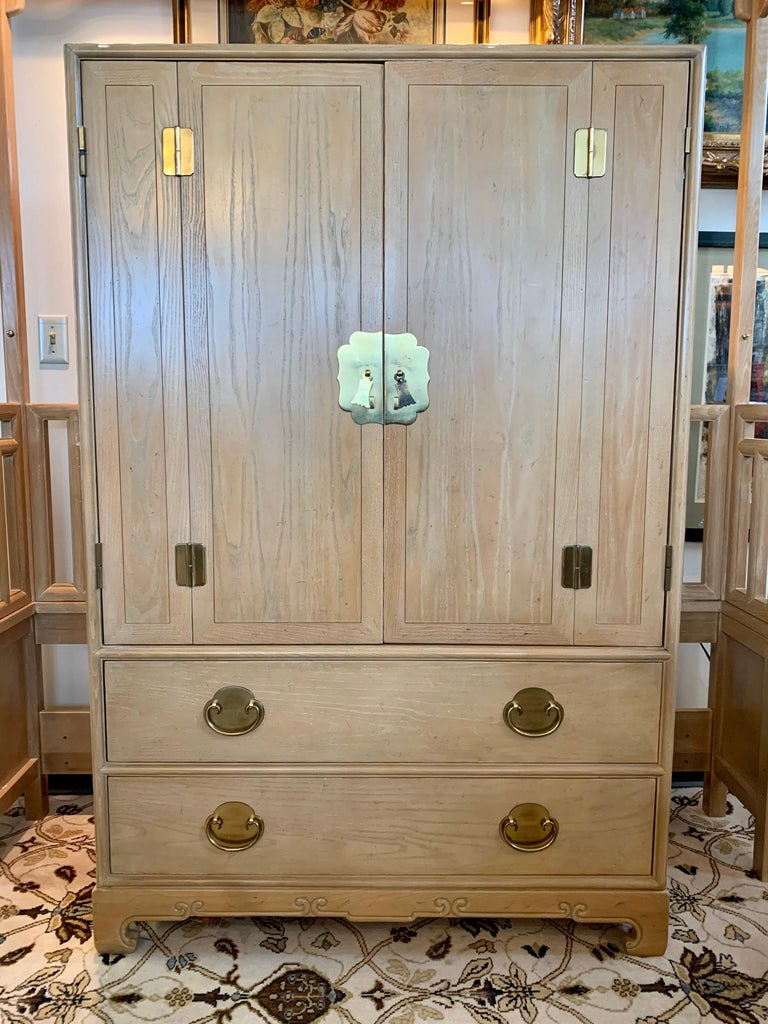 An elegant mens wardrobe dresser cabinet by Ray Sabota for Century Furniture Company in cerused oak, circa 1970s. Brass hardware and lovely motifs accent the piece. Functional scale will allow for use in many different rooms; think bedroom, living