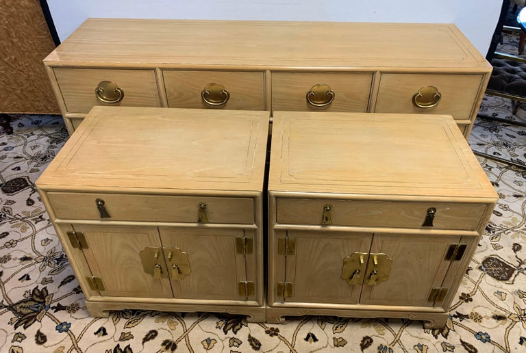 A gorgeous three piece matching set with a chest of drawers and two matching nightstands by Ray Sabota for Century Furniture Company, circa 1970s. Brass hardware and lovely motifs accent the pieces. Excellent vintage condition. Retains the maker