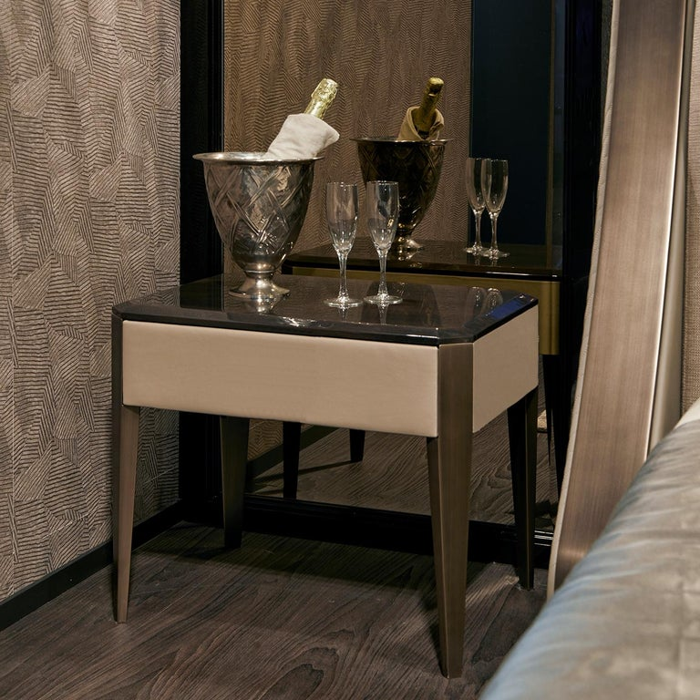 An exquisite design of clean architectural value, this bedside table flaunts an innovative combination of finishes and materials. With a structure made of poplar plywood upholstered of leather or synthetic leather upon choice, it features a